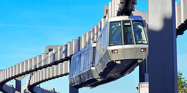 A grey suspension train meanders along a steel monorail at Düsseldorf International Airport, Germany.