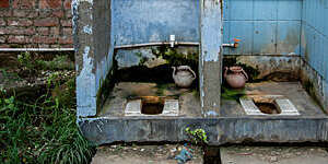 Two dilapidated open-air squatting toilets with scaling blue-painted walls.