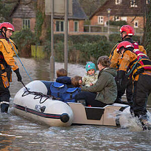 Family being rescued by the fire service after the River Derwent burst it
