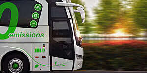 Close side view of a zero-emissions bus in motion against a blurred green background.