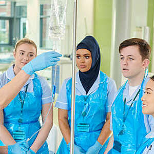 Four student nurses watch on as one student practices using an intravenous catheter.