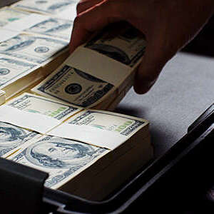 Close-up of hand putting bundles of hundred dollar bills in a briefcase.