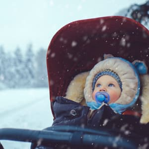 Baby boy in a stroller stares with bright blue eyes into a snowy winter landscape.