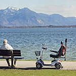 Back view of older man sitting on a bench on the waterfront with an electric wheelchair by his side.