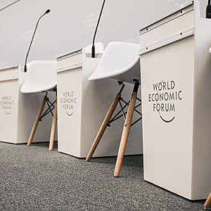 Lower section of a conference panel set showing cream-coloured chairs and tables bearing the World Economic Forum logo.