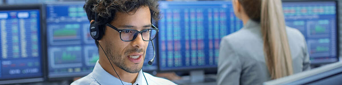 Face shot of a stock trader with headset making a sale in a busy stock exchange office.