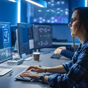 Side-face shot of a female programmer working in front of a computer screen in a data centre control room.
