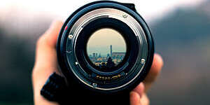 Close-up of camera objective with city view reflected in the lens.