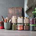 Jars of pulses and cereals stacked on a table alongside wooden bowls and kitchen utensils.