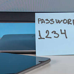 Weak password on flying note with a keyboard in foreground.