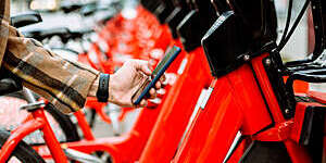 Close-up of a man's hand using a smartphone to rent a red bicycle from an urban bicycle sharing station.