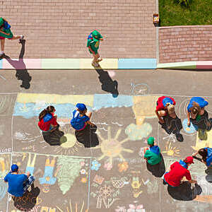 Overhead view of kids coloring a picture with colored chalk in driveway.