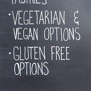 "Close-up of slate notice board advertising ""vegetarian and vegan options""."