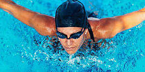 Woman wearing swimming goggles, swimming in a pool.