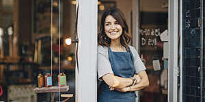 Female owner of a delicatessen smiles confidently as she stands in the doorway of her establishment.