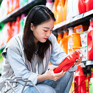 Close-up of woman holding a red bottle of washing detergent beside a well-stocked supermarket shelf.