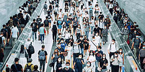 Stream of commuters with protective face masks during rush hour at a busy subway station.