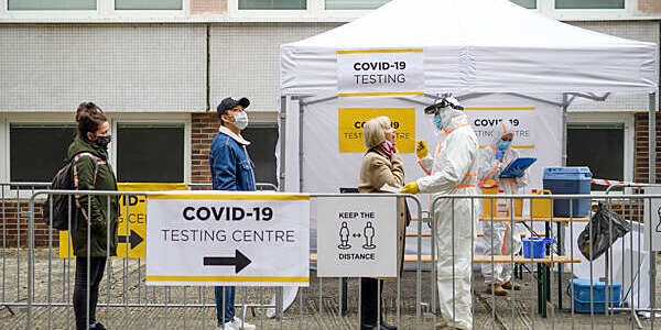 Three people line up on the street at a COVID-19 testing centre where a medical staff member in full white protective overalls performs the PCR swab test.