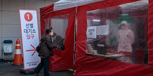 An elderly woman enters a coronavirus testing booth outside the Yangji Hospital in Seoul, South Korea.