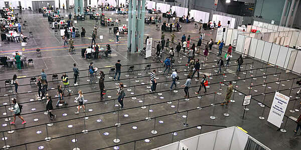 Plunging view of people lining up to receive the COVID-19 vaccine in a large hall of the Jacob K. Javits Convention Center, Manhattan, New York City.
