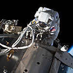 Top view of NASA astronaut Michael Hopkins servicing communications gear on the International Space Station's Columbus laboratory module, against a backdrop of darkness and blue Earth outline.