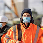 Head-on view of shipyard worker in a bright orange safety jacket and disposable mask, surrounded by out-of-focus co-workers.