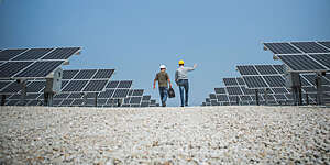 Back view of two technicians with safety helmets holding a work discussion as they walk across a field of solar panels set against bright blue skies.