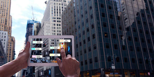 Hand holding a tablet with an augmented reality app showing nearby shops and eateries in New York City.
