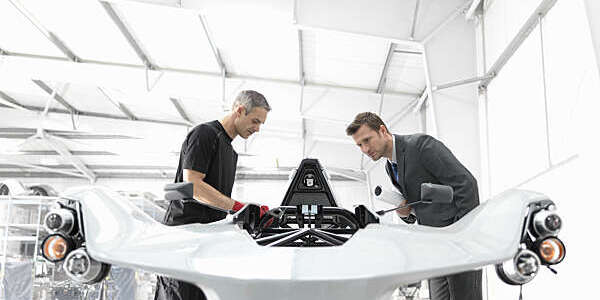 Engineer and automotive designer inspecting part-built supercar in car factory.