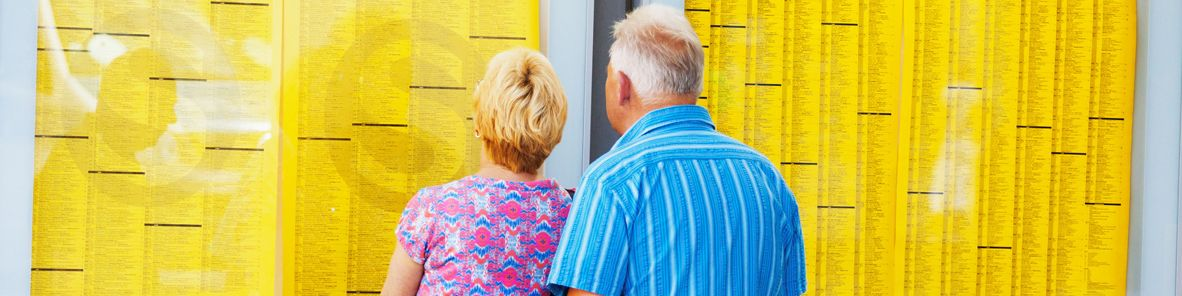 A senior couple is watching and reading timetable for local trains.