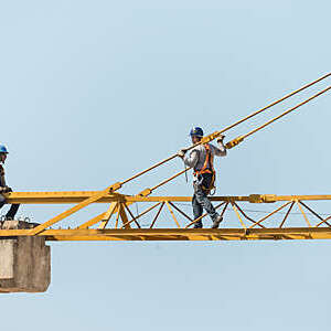 Two workers on top of a tower crane.