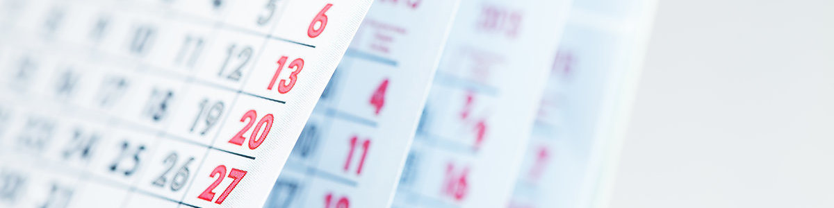 Months and dates shown on a calendar whilst turning the pages with shallow depth of field