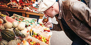french man smelling on tomatoe at food stall in Paris street