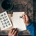 close up of old hands writing chinese calligraphy characters with india ink on paper