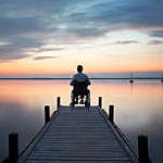 Senior man sitting in wheelchair at the end of lakeside jetty watching majestic cloudscape at dusk