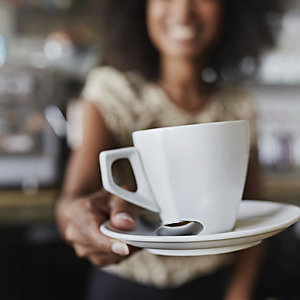 Woman serving a cup of coffee