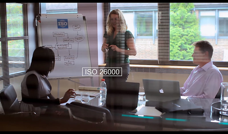 People in office look at flip-chart and discuss ISO 26000